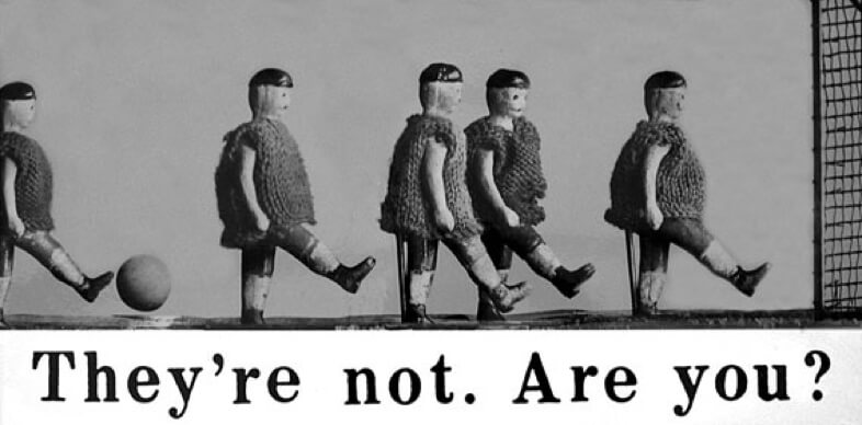 Five toy football players with a ball and the caption: They're not. Are you?